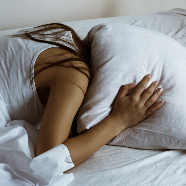 a tired young women trying to sleep with a pillow covering her head