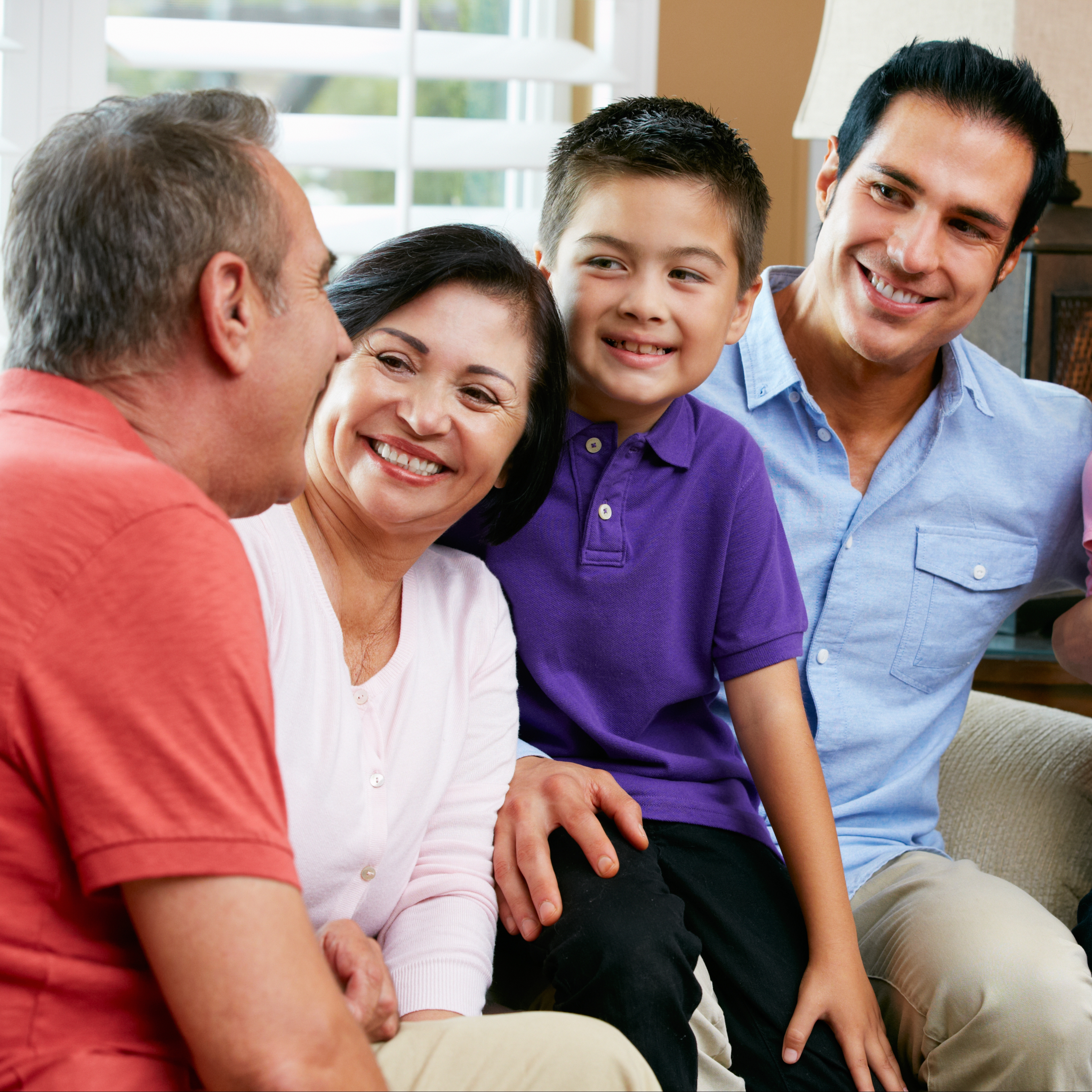 a three generational family sitting on a couch laughing and smiling - diversity
