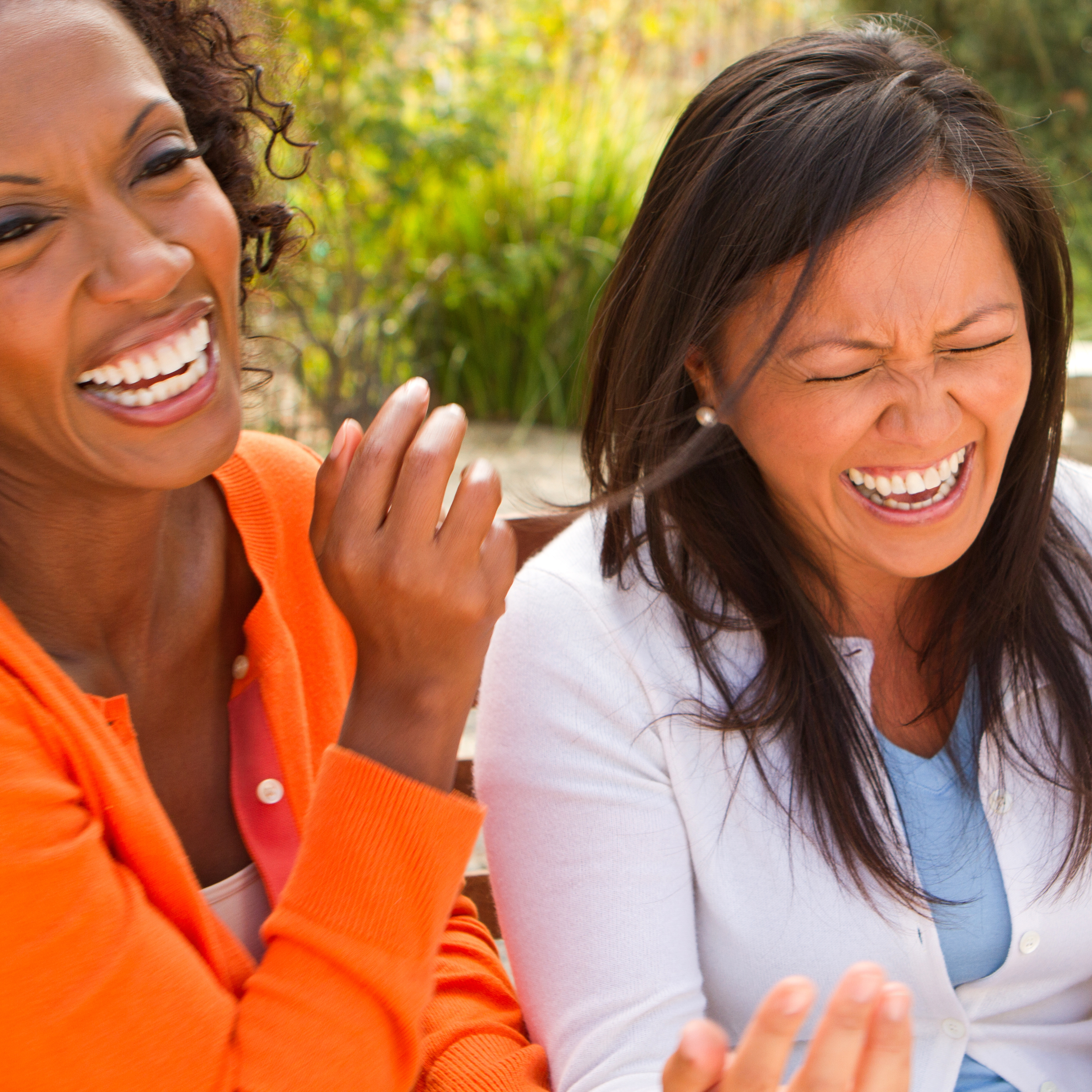 two middle-aged women friends smiling, laughing and having fun together