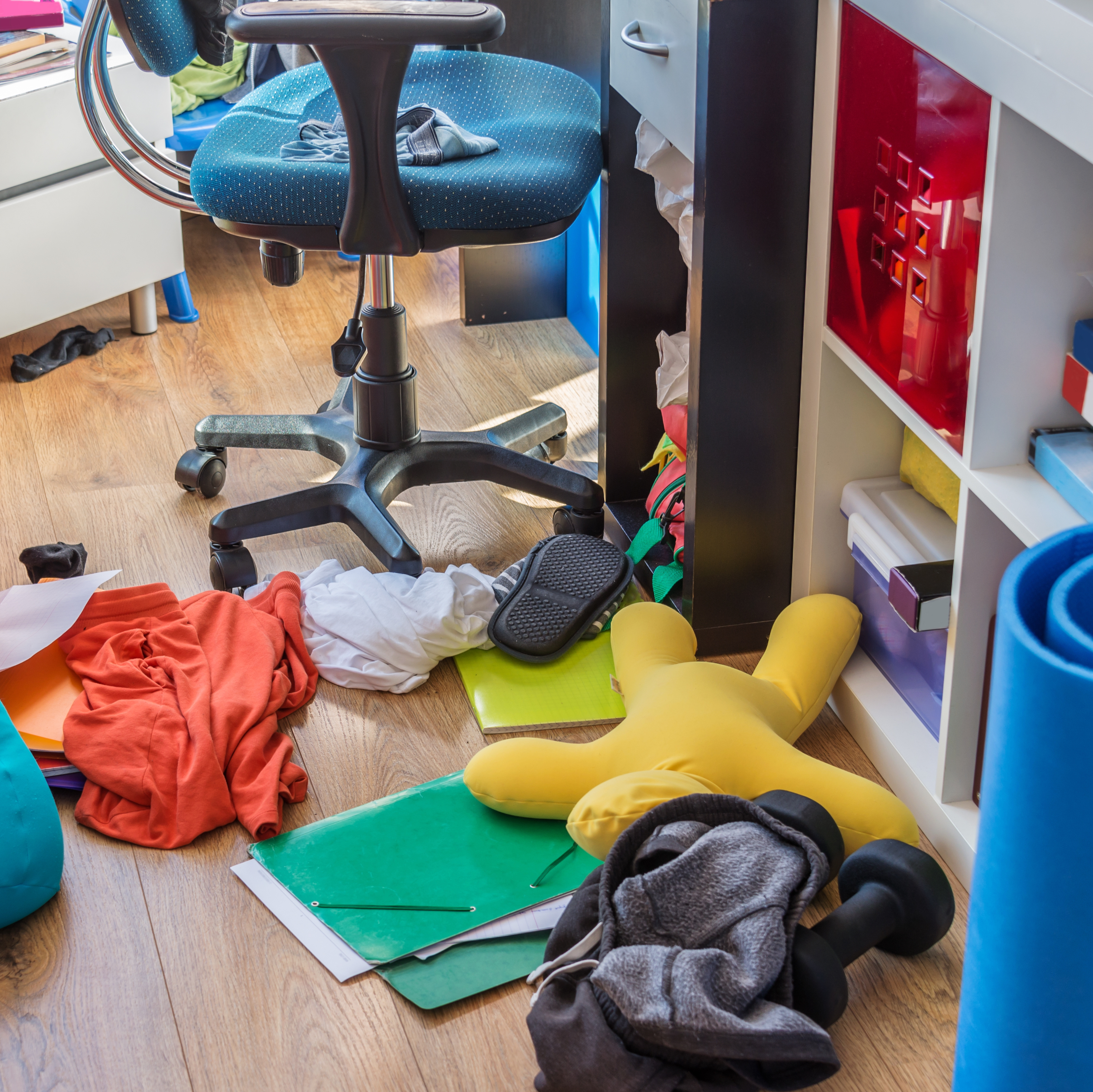 an untidy, messy, cluttered room with clothes and items scattered on the floor