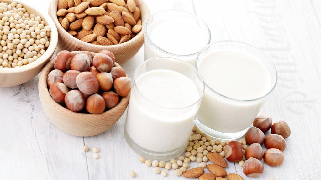 Tazones de madera con soja, almendras y avellanas, más tres vasos con las leches correspondientes.