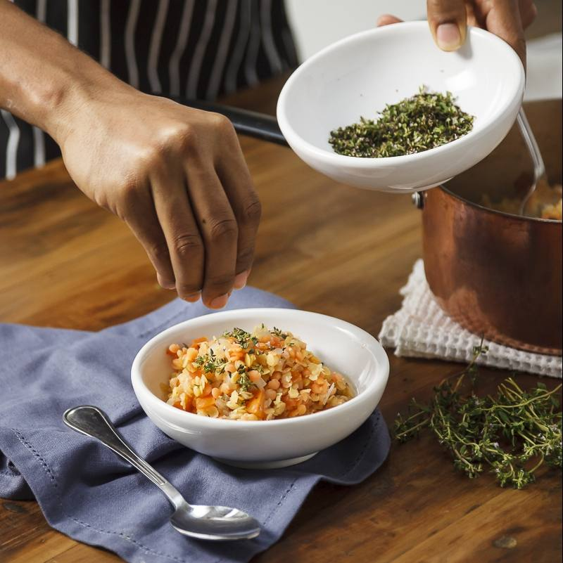 a person sprinkling herbs on a bowl of lentil soup or stew