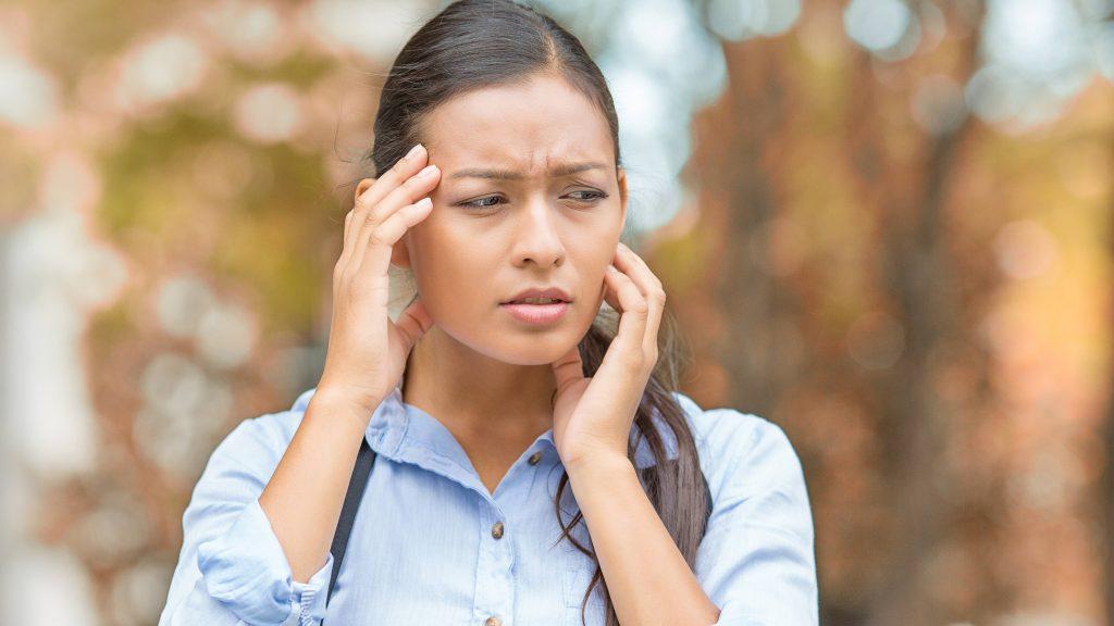 Foto de una mujer con las manos en la cabeza por el dolor y con el trasfondo de un bosque en el otoño