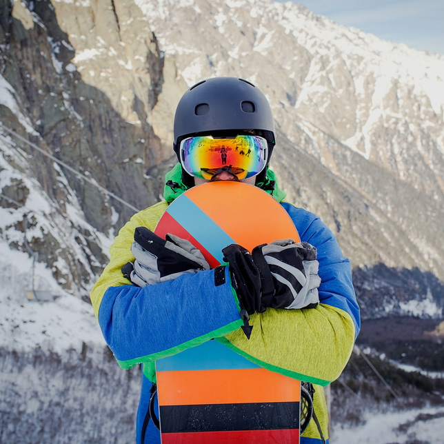 a snowboarder on a snowy mountainside, holding a snowboard