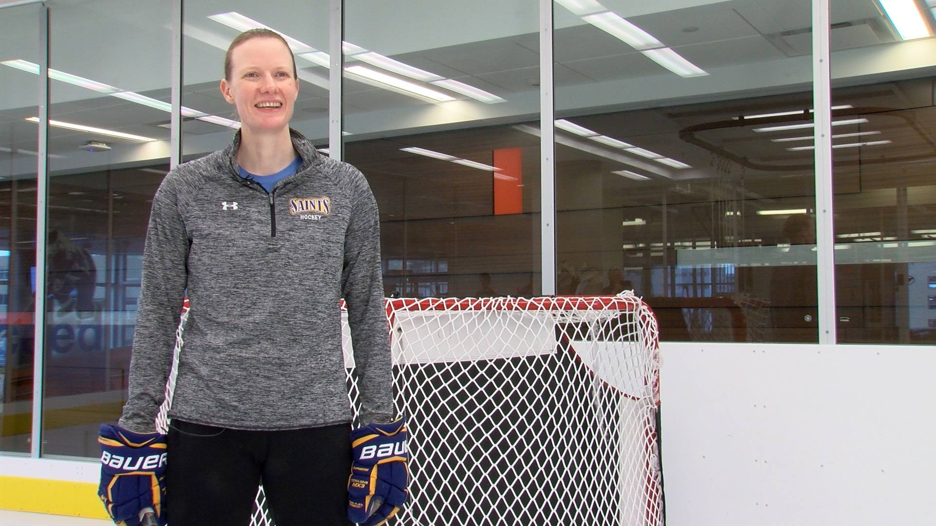 Julianne Vasichek standing in front of a hockey goal net.