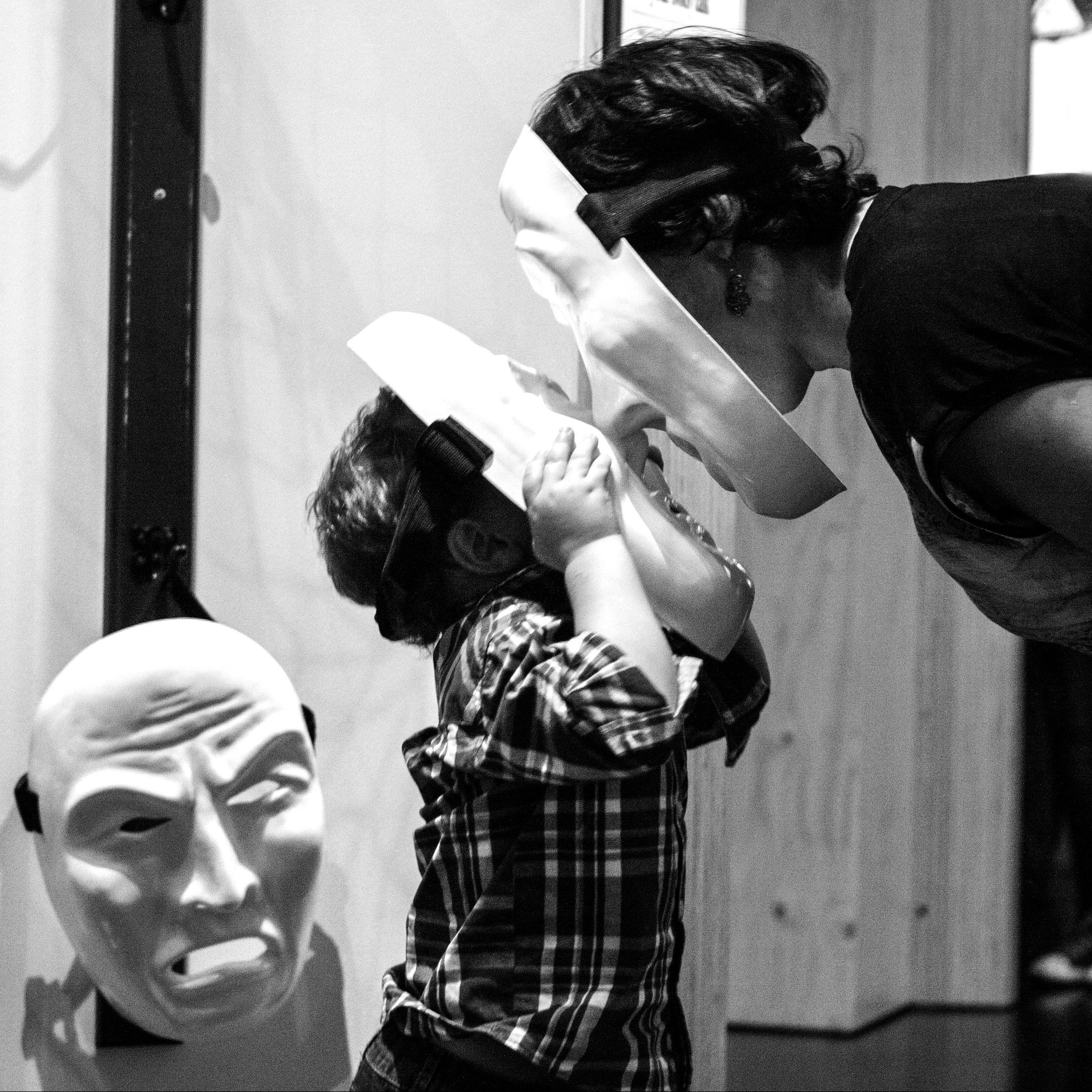 a child and an adult at the mental health exhibit wearing masks