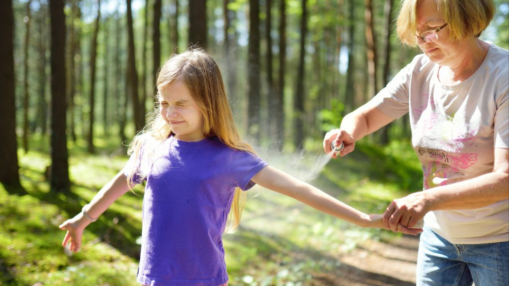 a young girl out in the woods getting tick or bug spray on her arm