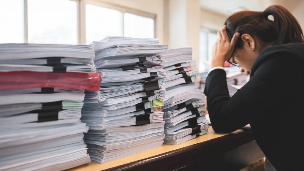 a young business woman looking stressed, holding her head in her hands at a work desk piled high with paperwork