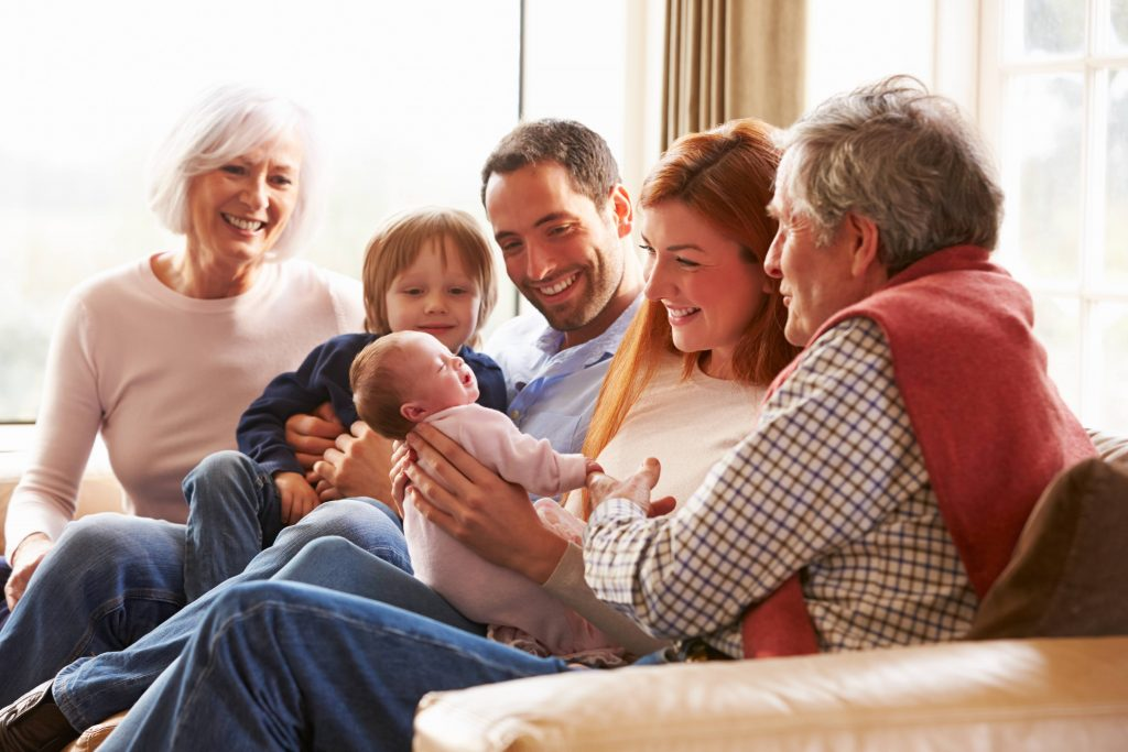 a happy, smiling multigenerational family sitting on a sofa, including grandparents, parents, young child and baby