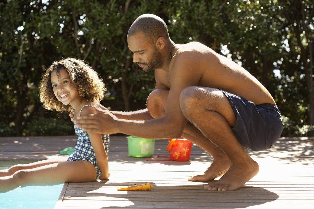 a young girl sitting on the side of a swimming pool with an adult man, perhaps her father, putting sunscreen on her