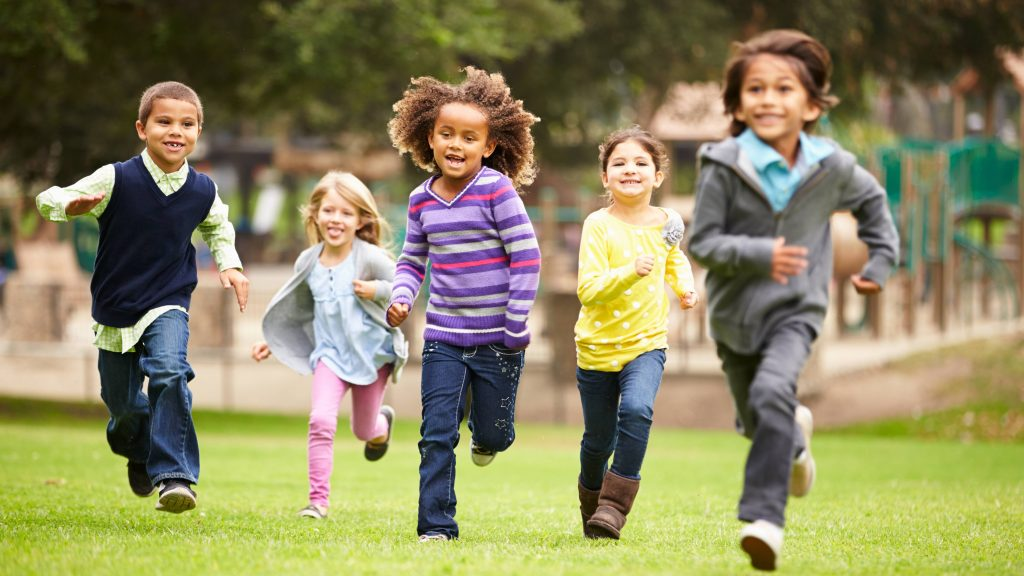 a group of happy children running and smiling near a playground