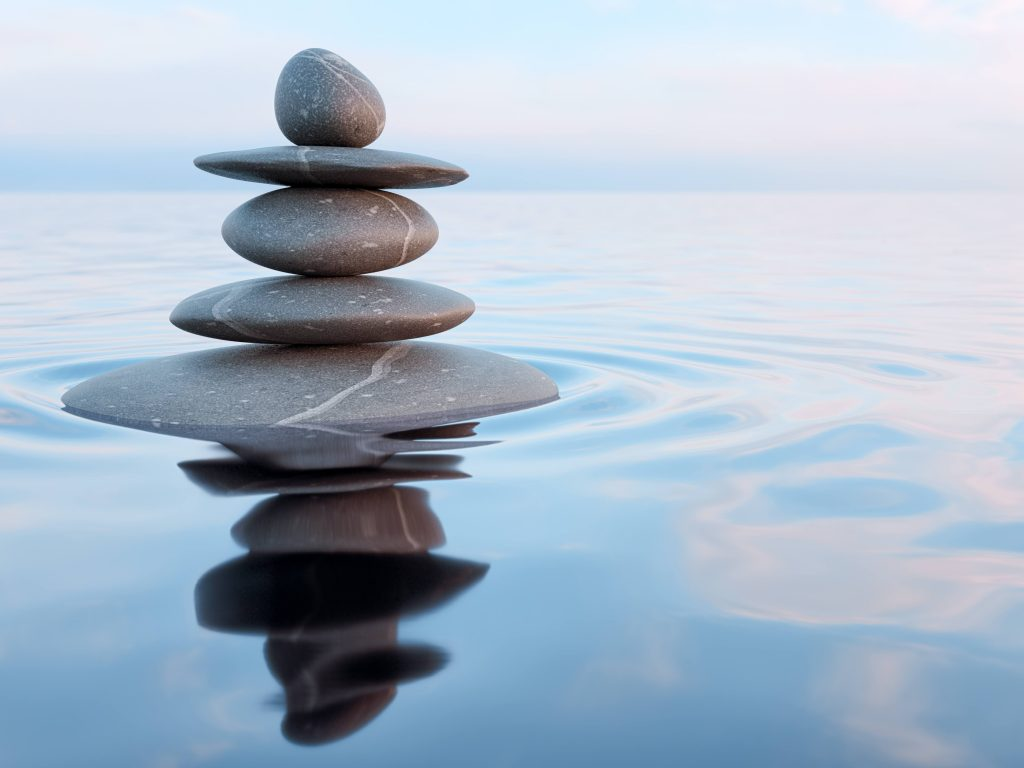 a stack of smooth stones in a pool of water, illustrating relaxation, meditation, balance, peace