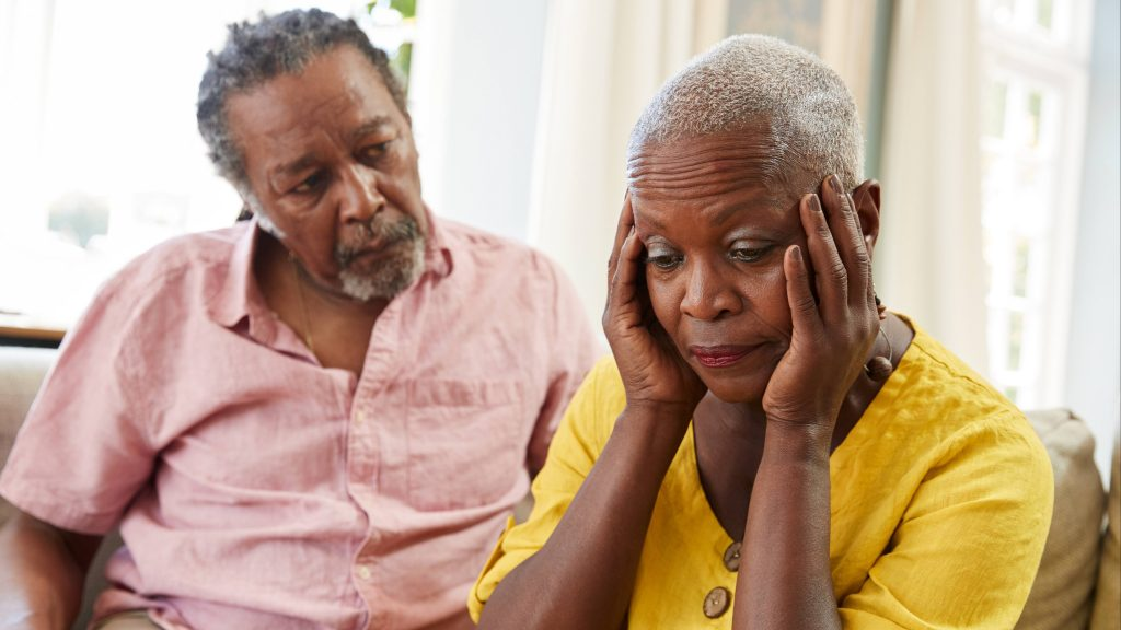 a sad and worried looking African Americanmiddle-aged couple sitting on a couch, with the woman holding her head