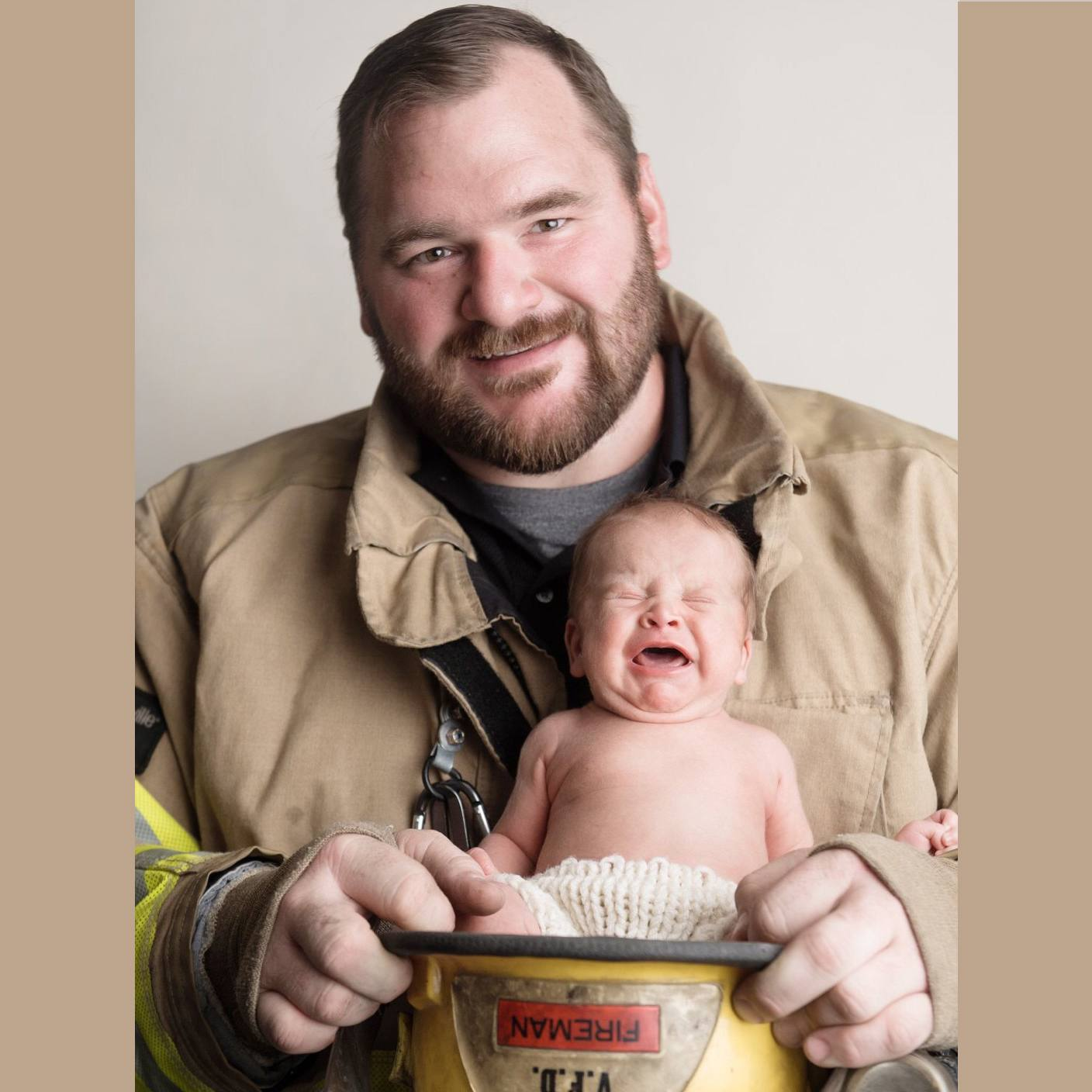Tumor patient Derin Gebhardt dressed in firefighter gear holding his young child in his fire hat.