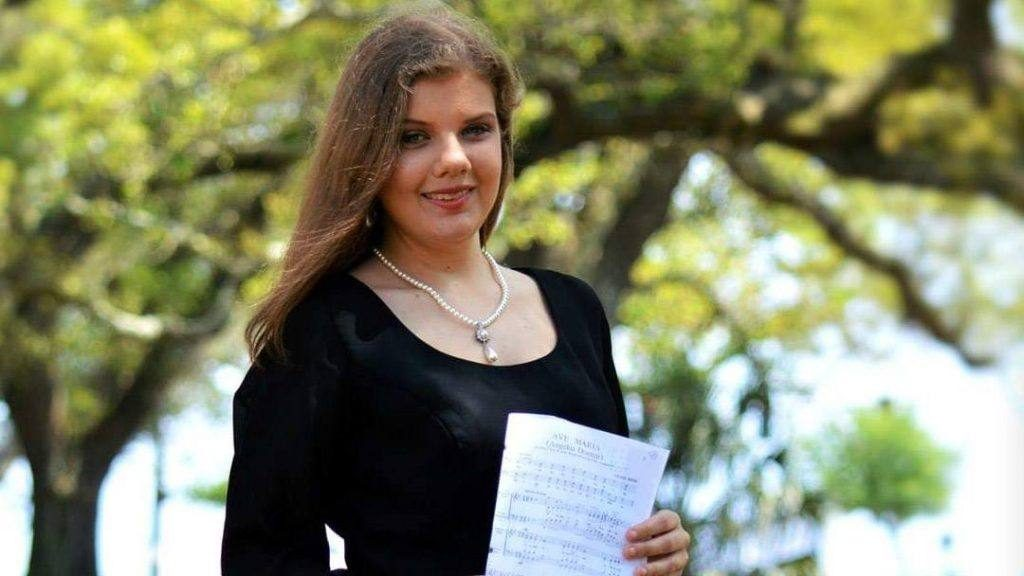 Sharing Mayo Clinic patient Mackenzie Rolison wearing a black choir dress and holding a sheet of music