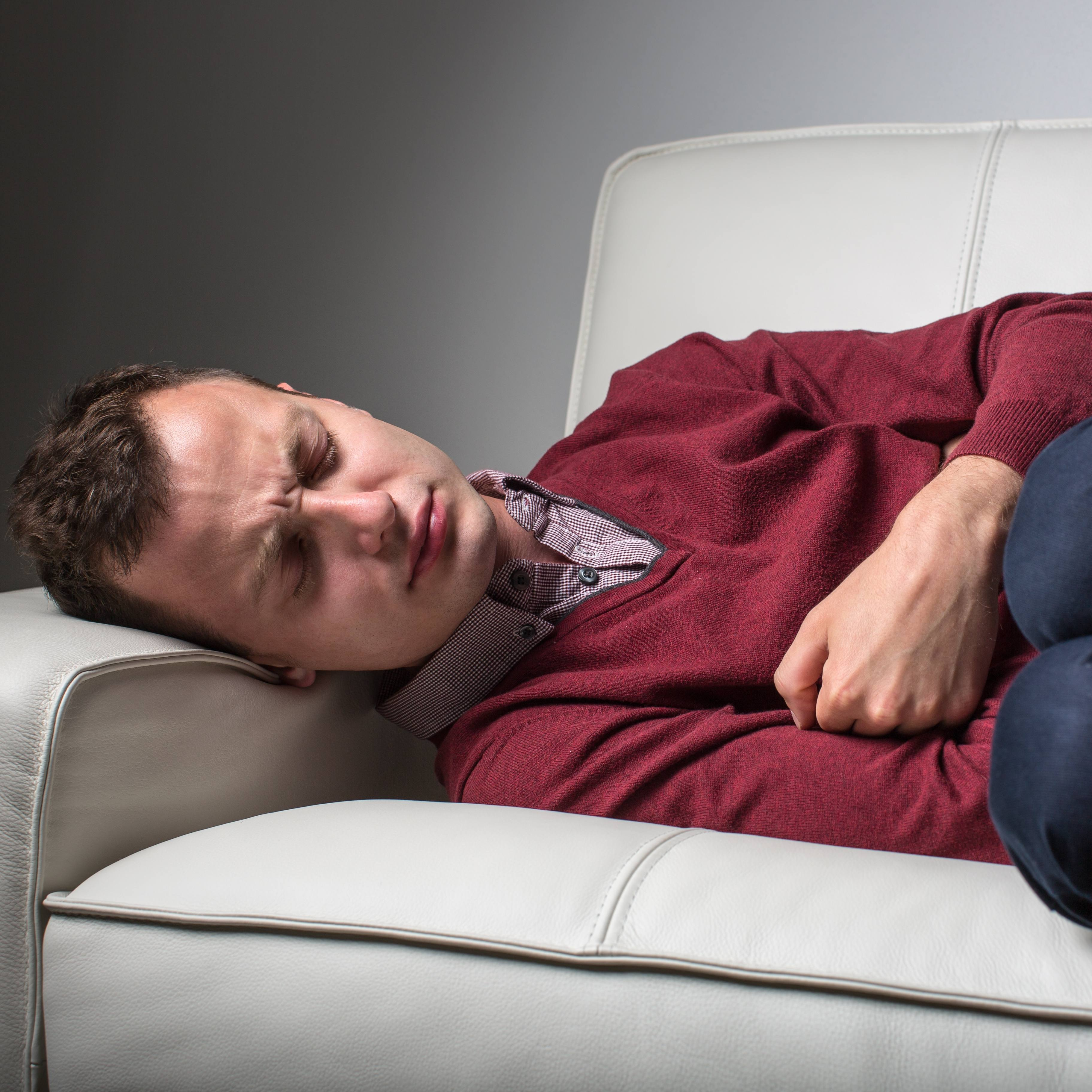 man lying on a couch suffering from severe stomach pain