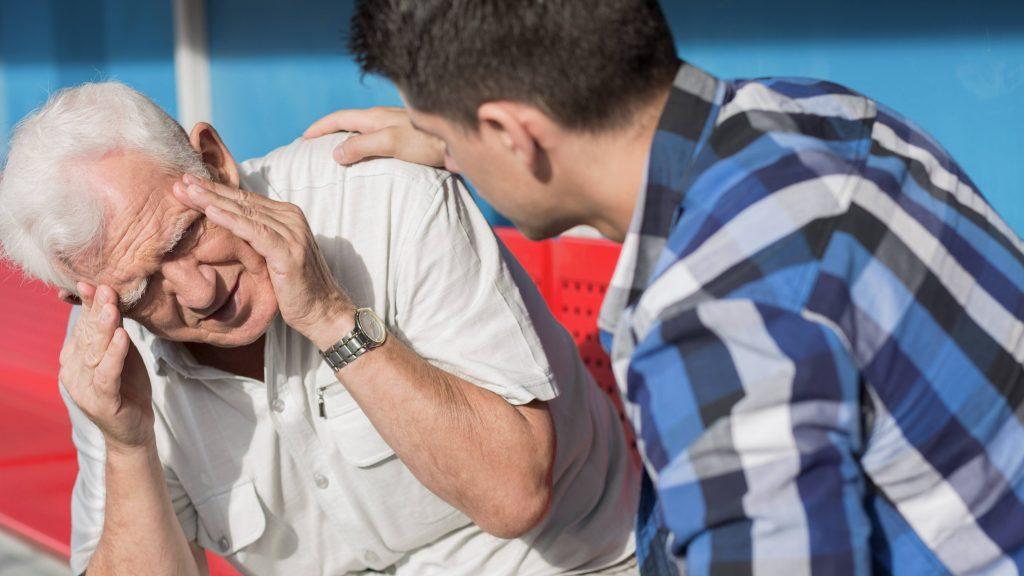 Un anciano tiene mareo y un joven está preocupado junto a él