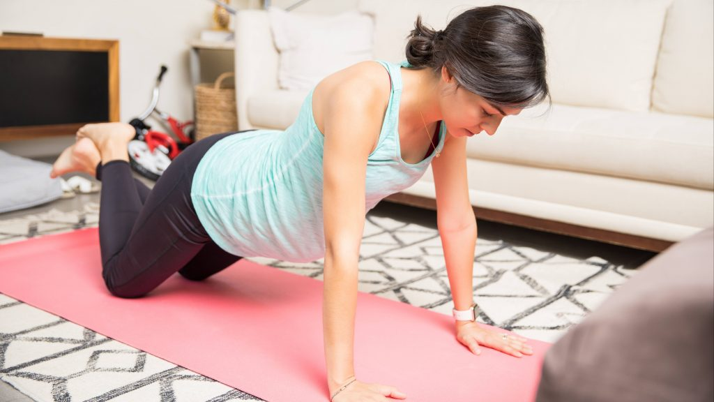 a pregnant Caucasian woman exercising on a yoga mat