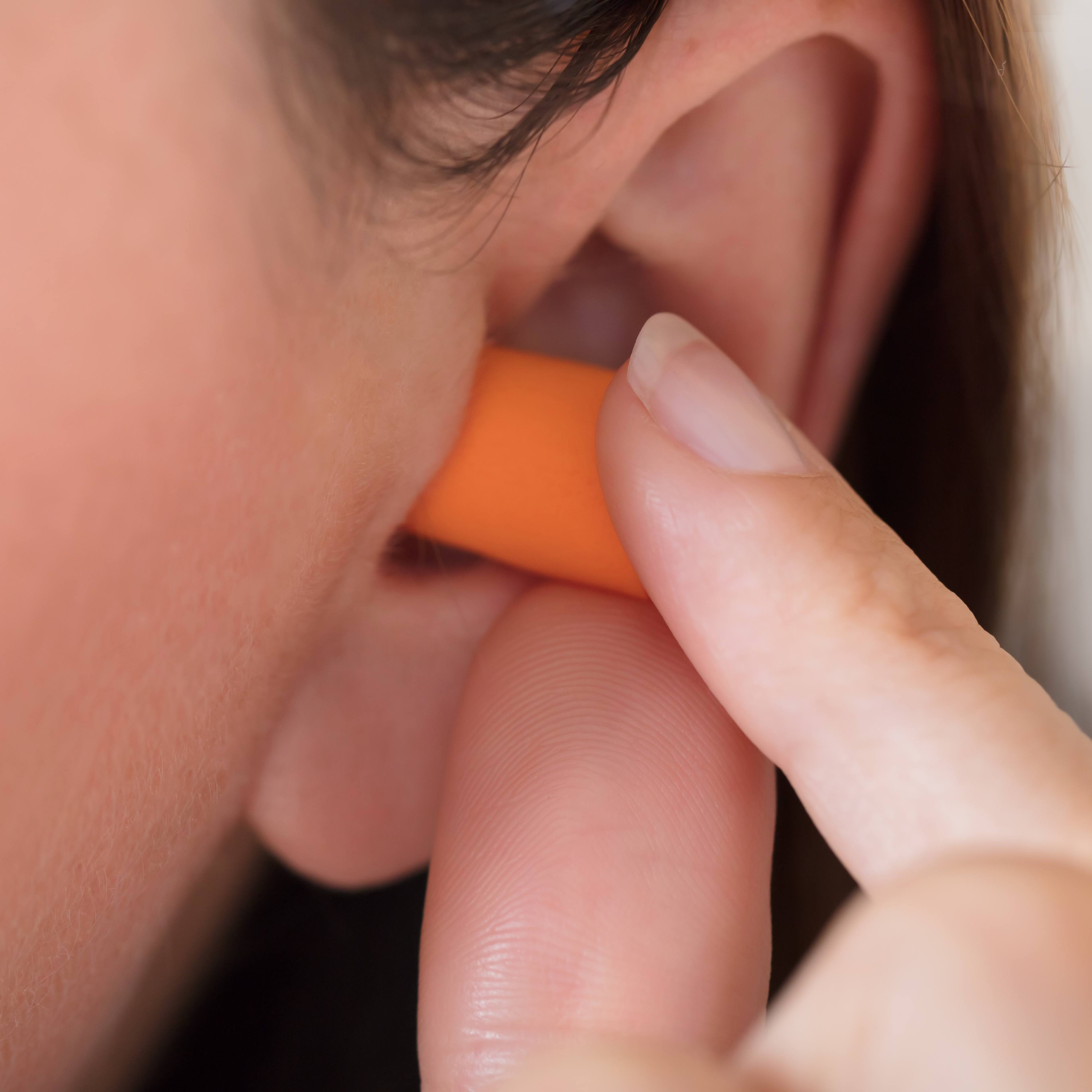 a young woman putting an earplug in her ear to help block out loud sounds and noises to protect her hearing.