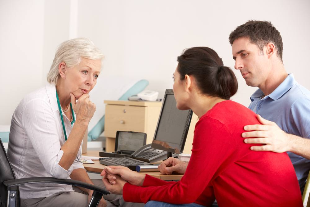 a worried middle-aged couple talking with a health care provider in her office