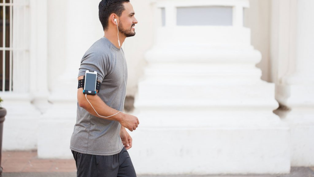 Un joven camina por la ciudad mientras escucha música con los audífonos del teléfono inteligente