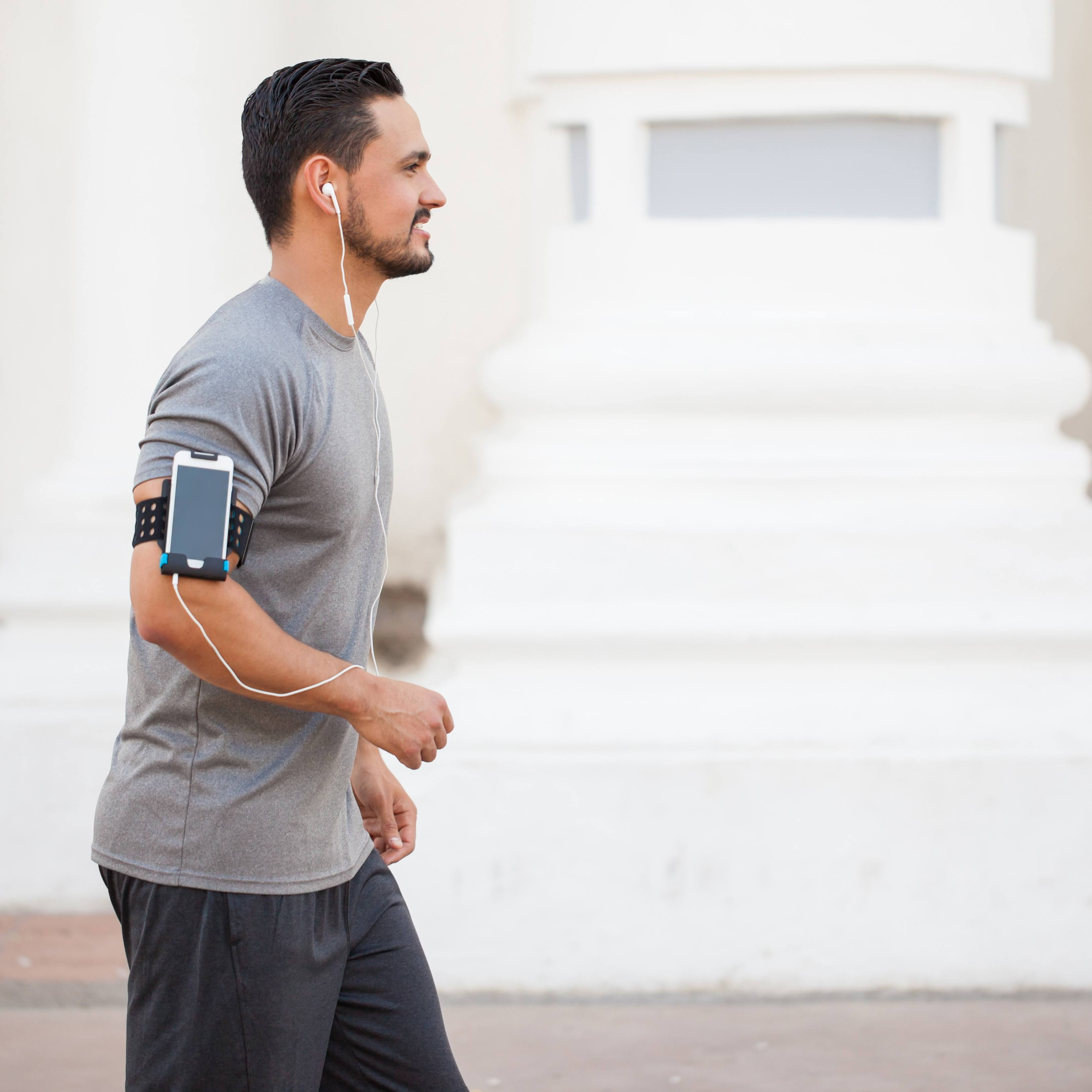 Young man walking in the city while listening to music with earbuds and a smartphone