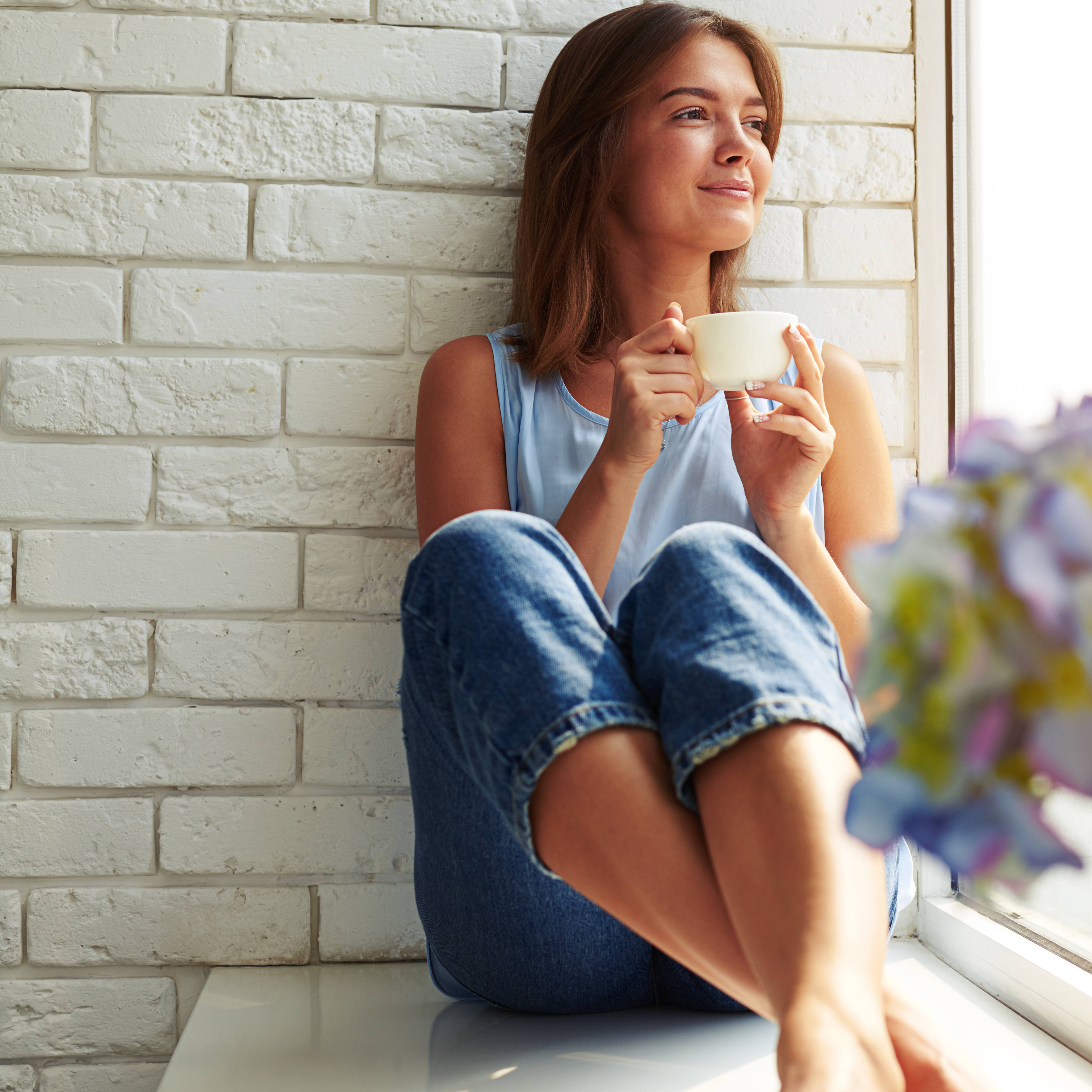 a smiling young woman, sitting in a sunny windowsill, sipping coffee and looking outside