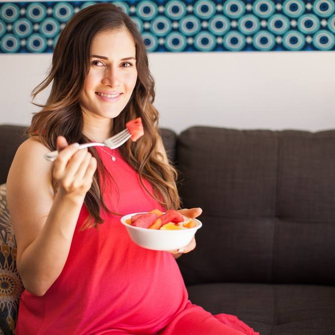 pregnant woman eating healthy food in her living room and smiling