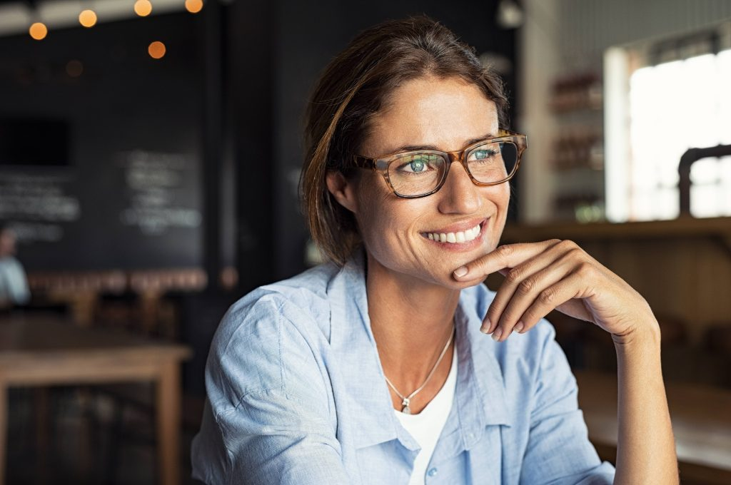 a close-up of a smiling middle-aged woman in glasses, sitting in a coffee shop