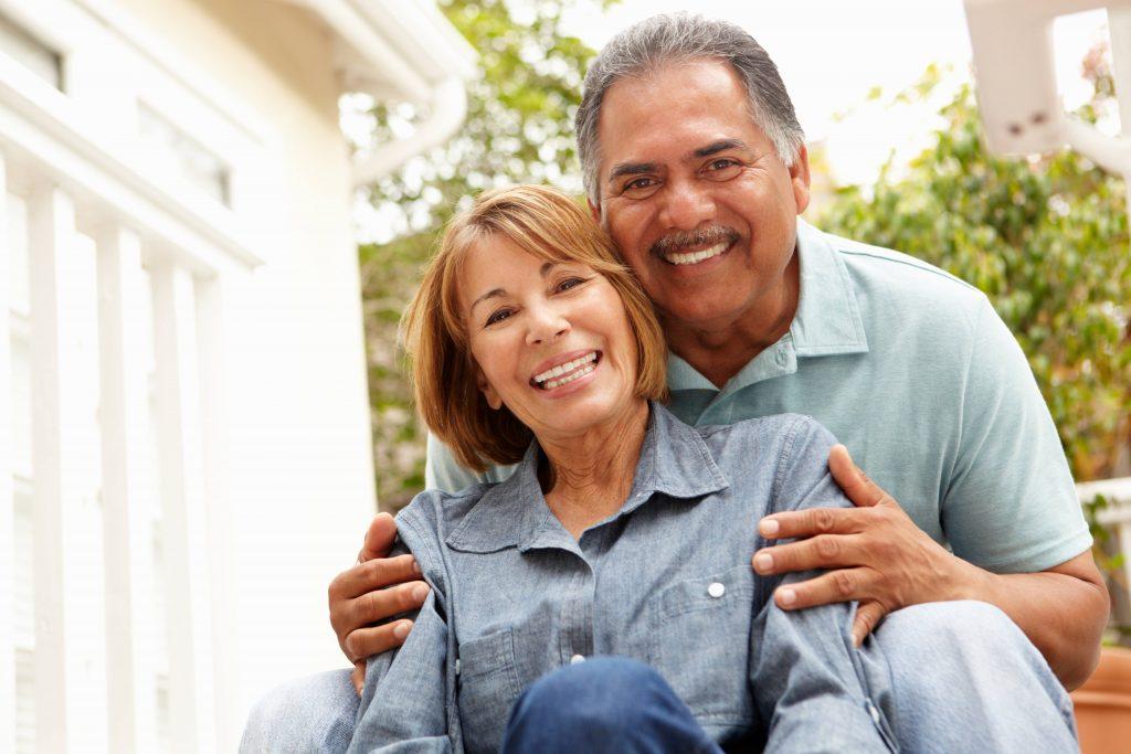 a smiling older couple sitting together outside