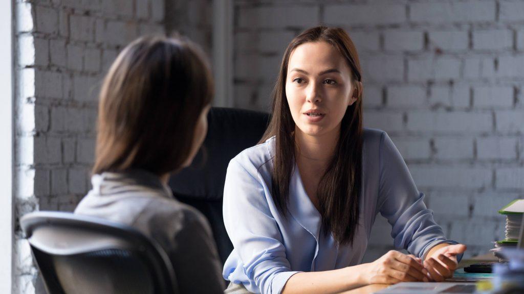 Una mentora profesional habla con una mujer joven