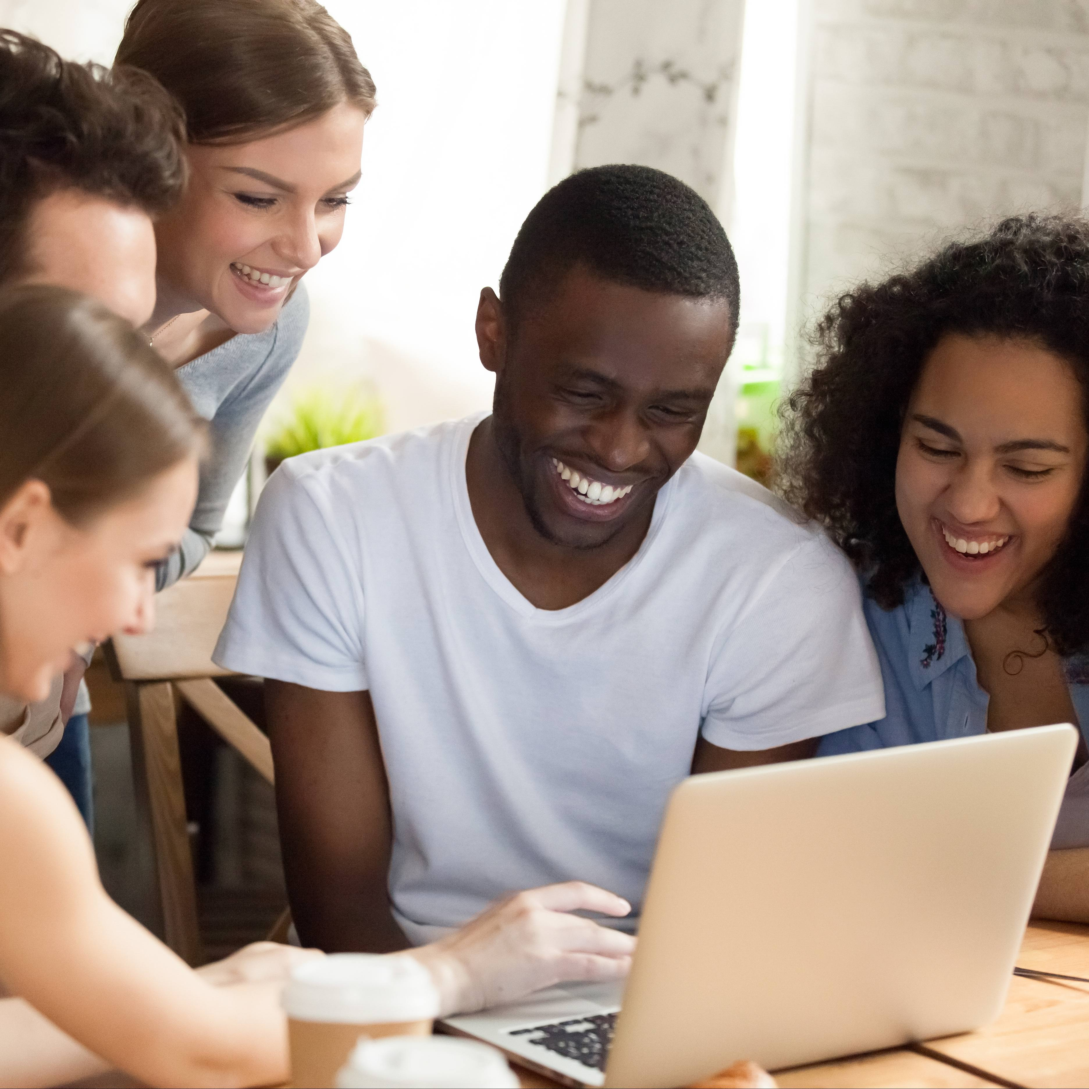 a group of young adult, perhaps university or college students gathered around a laptop computer, smiling, laughing and having fun together