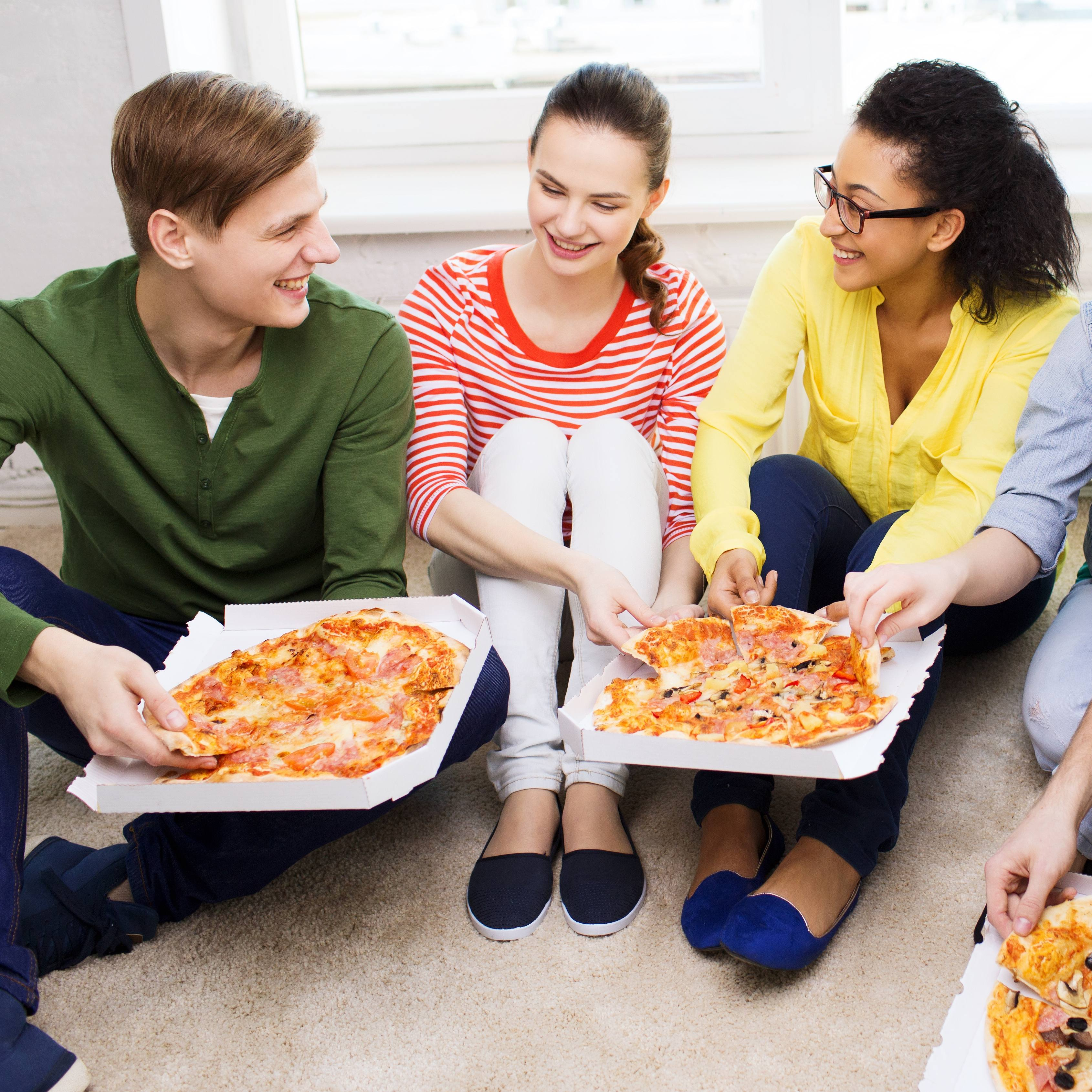 a group of friends, students, young people sitting together on perhaps a dorm room floor, laughing, smiling and eating pizza
