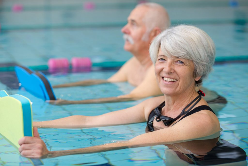 a smiling older woman in the pool in a swimming or water fitness class