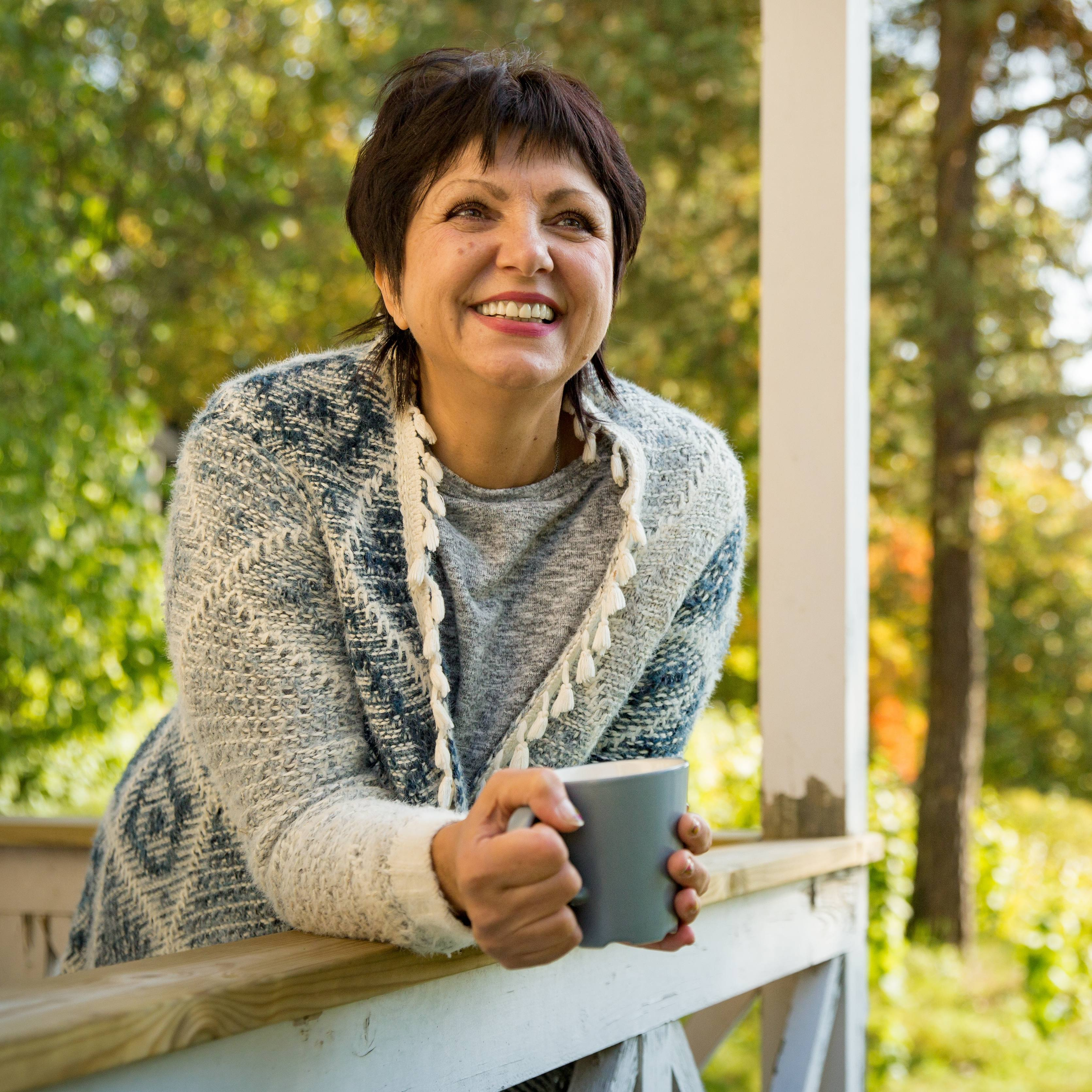 a middle-aged woman in a sweater, smiling and leaning over a porch or balcony railing, holding a cup of coffee