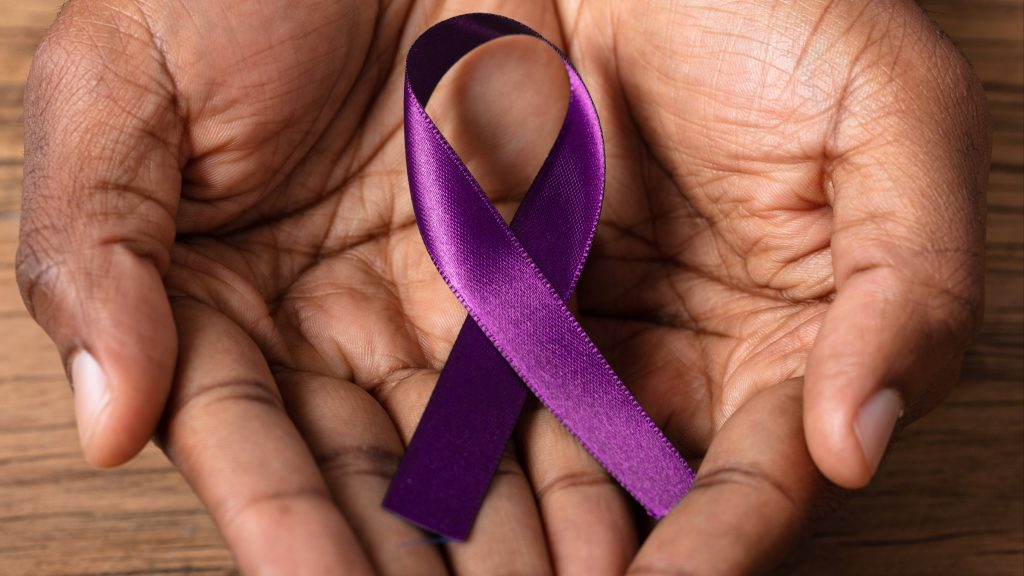 a person's hands cupped and holding a purple ribbon representing Alzheimer's disease, memory loss, dementia, cognitive function