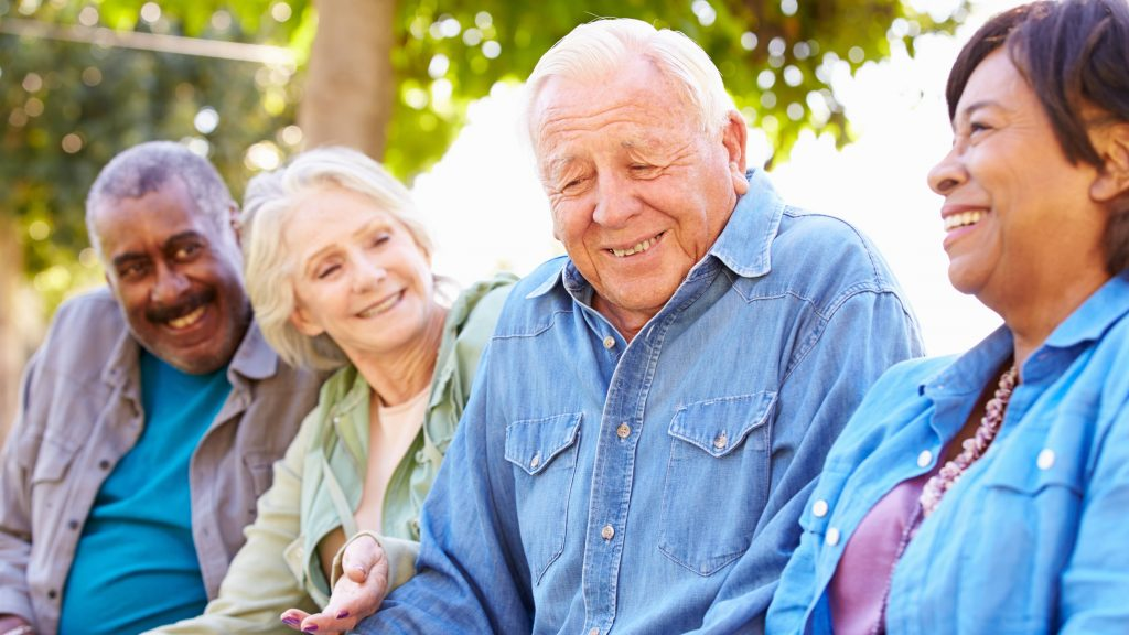 a happy group of older people, perhaps friends, laughing and smiling with each other