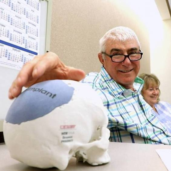 Sharing Mayo Clinic brain tumor patient Tony DeGange with his wife in a medical office, looking at skull model