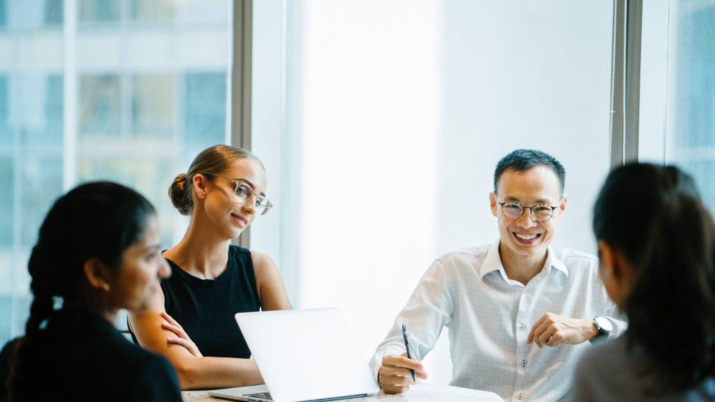 Un equipo diverso de personas de negocios tienen una reunión productiva y eficiente.
