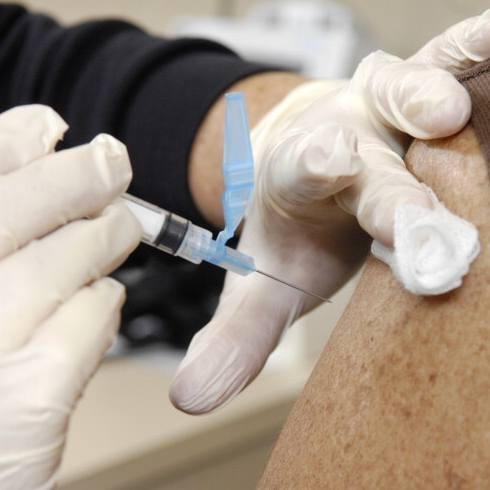 a Mayo Clinic medical staff person administering a flu shot in a Caucasian woman's sleeveless arm