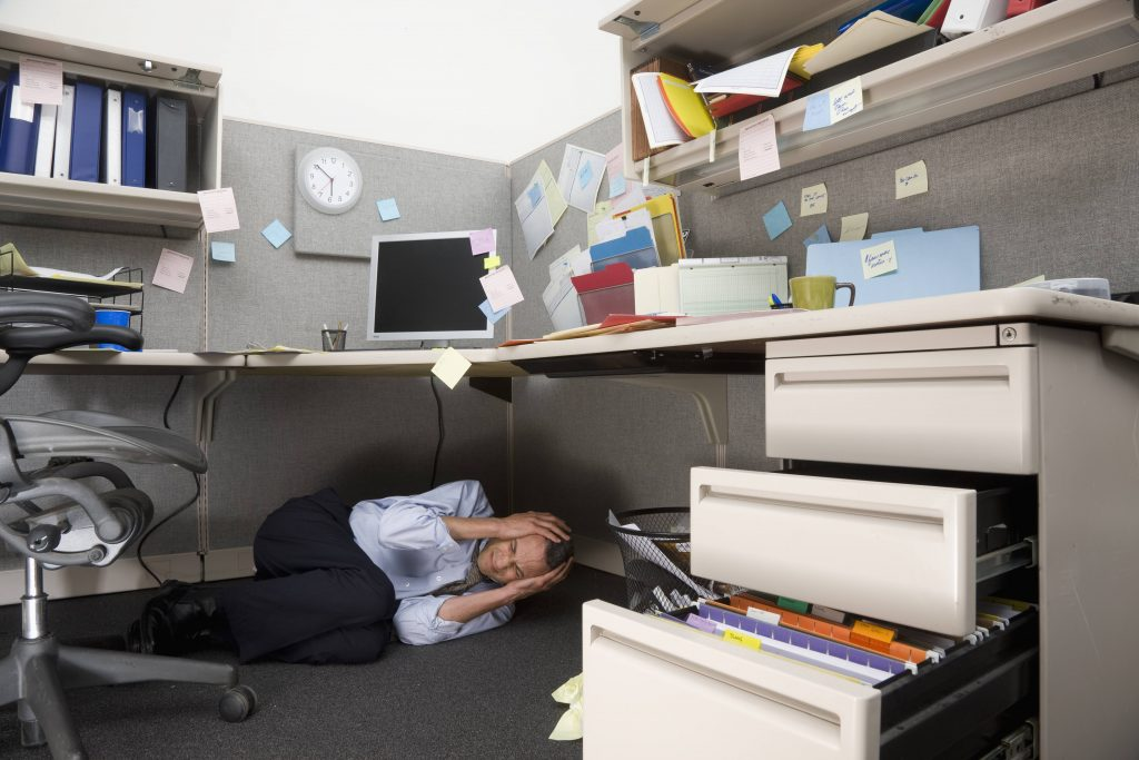 a man grimacing and curled up on the floor under a messy, cluttered desk