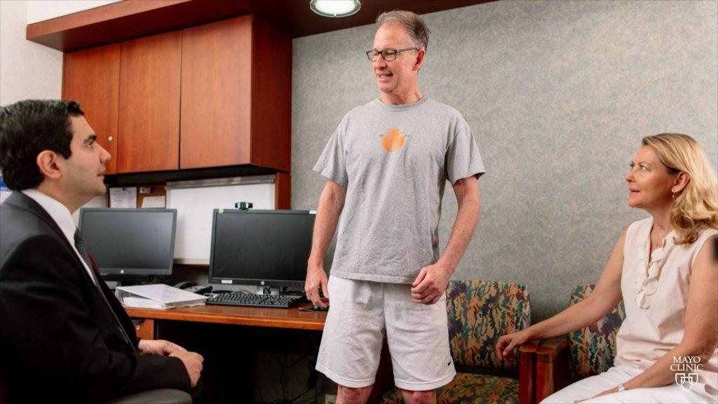 Chris Barr, paciente del ensayo sobre células madre, vestido con pantalones cortos y camiseta aparece sonriente y de pie en la sala de exámenes del Dr. Mohamad Bydon, ante la mirada atenta de su esposa Debbie Barr.