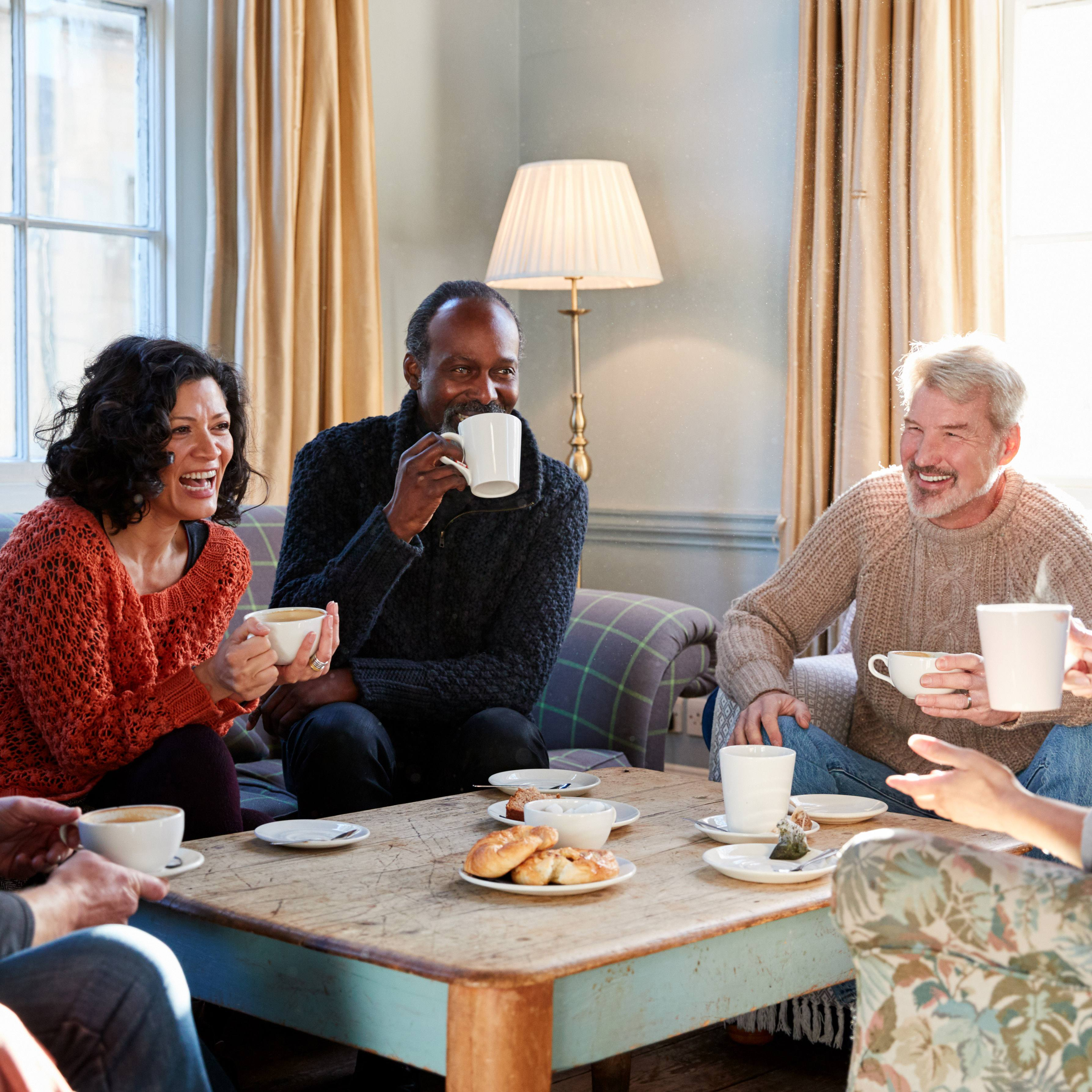 a group of smiling middle-aged men and women sitting around a low table in a living room, enjoying coffee, tea and pastries