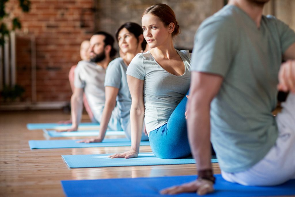 stock image of a row of adults sitting on yoga mats, turning towards their back
