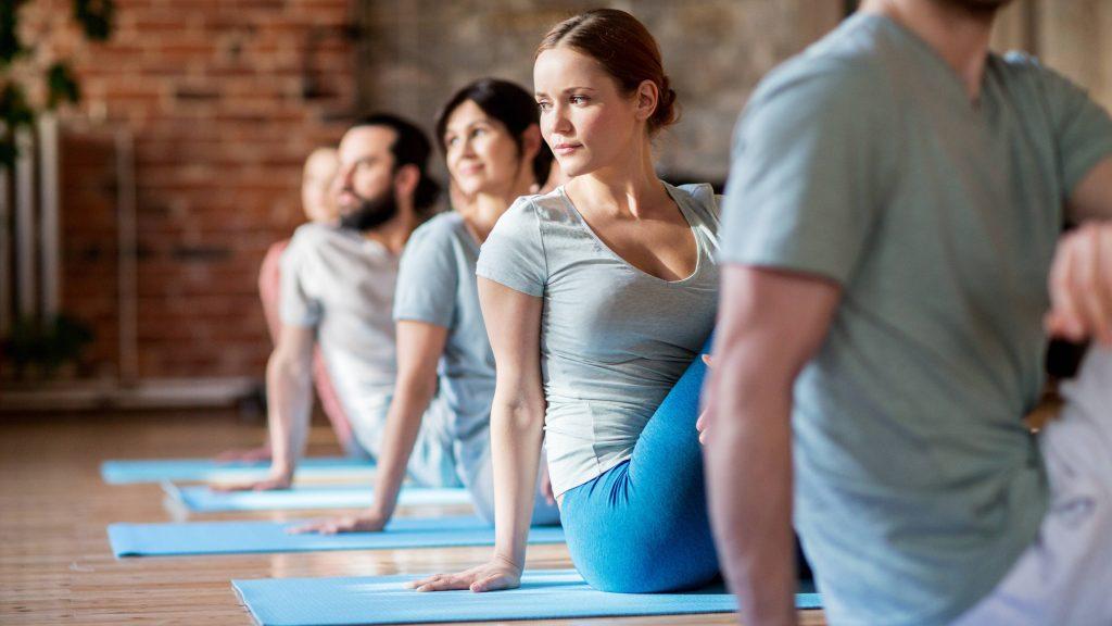 Hombres y mujeres hacen yoga sentados