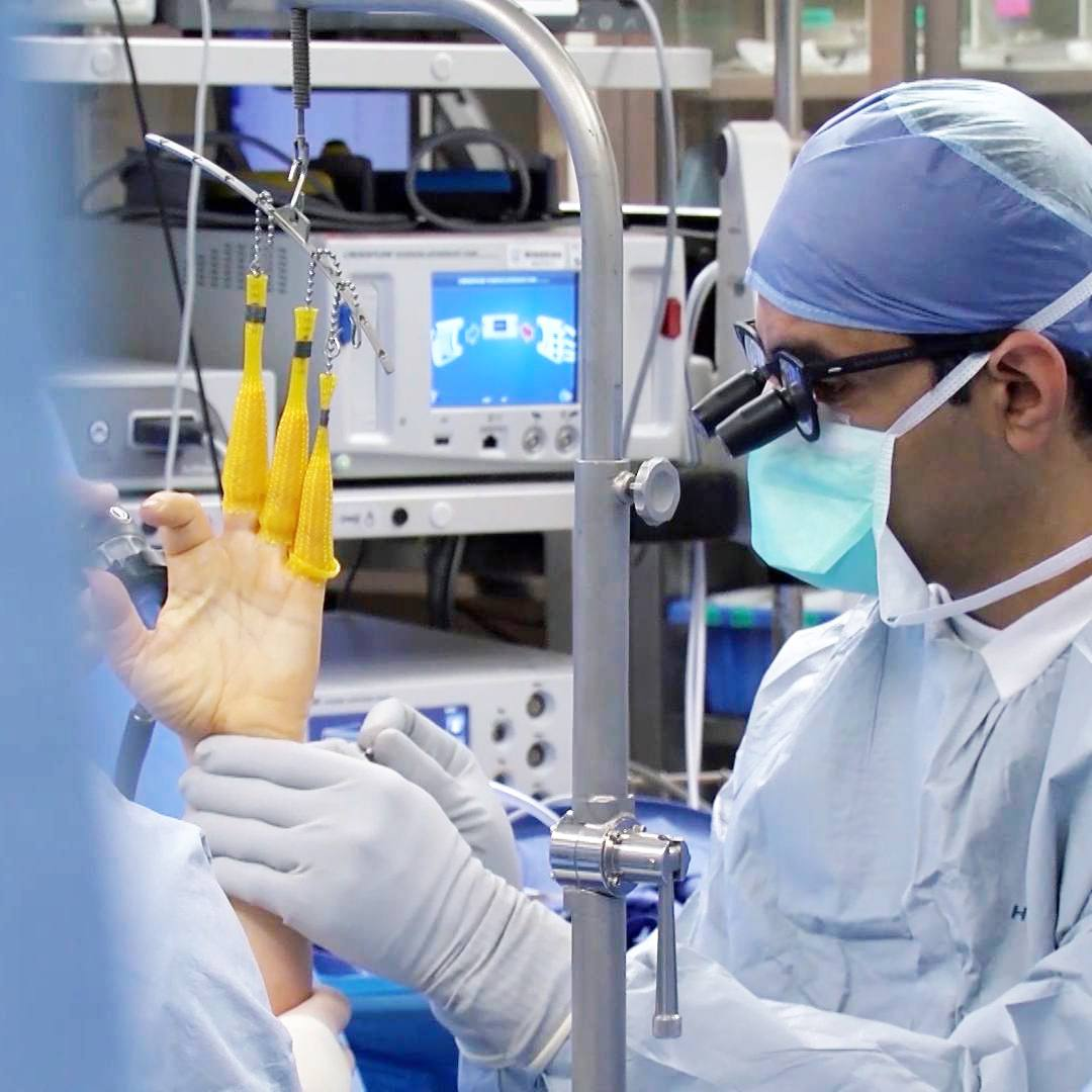 An orthopedic surgeon operates a wrist surgery.