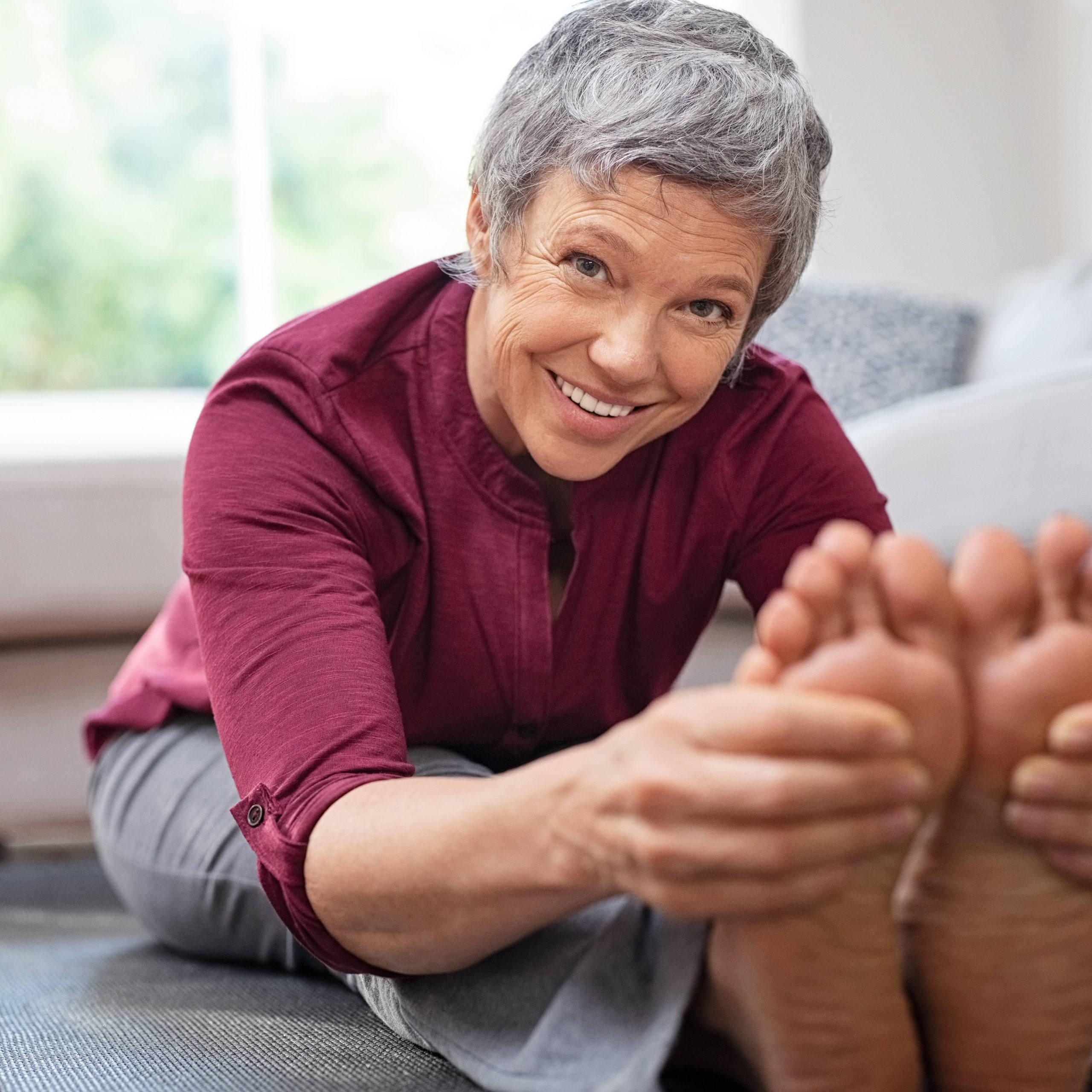 a smiling older woman seated on a yoga mat, doing stretches