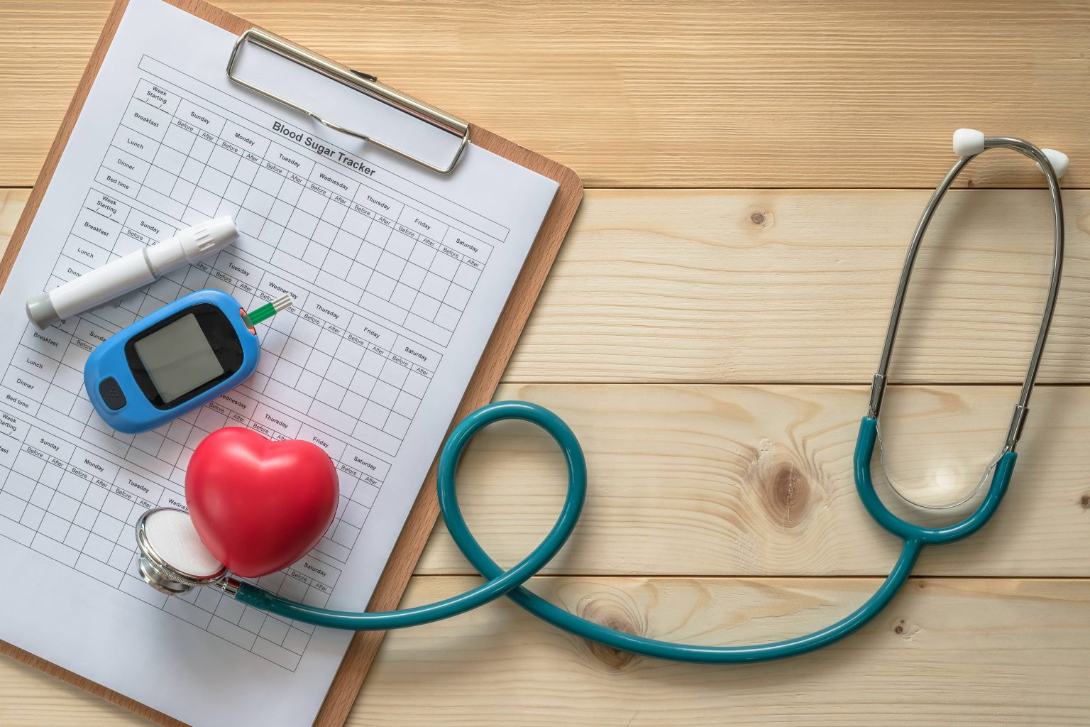 blood sugar tracker form on a clipboard, insulin injector pen, handheld digital gadget for reading blood sugar, foam heart and stethoscope artistically arranged