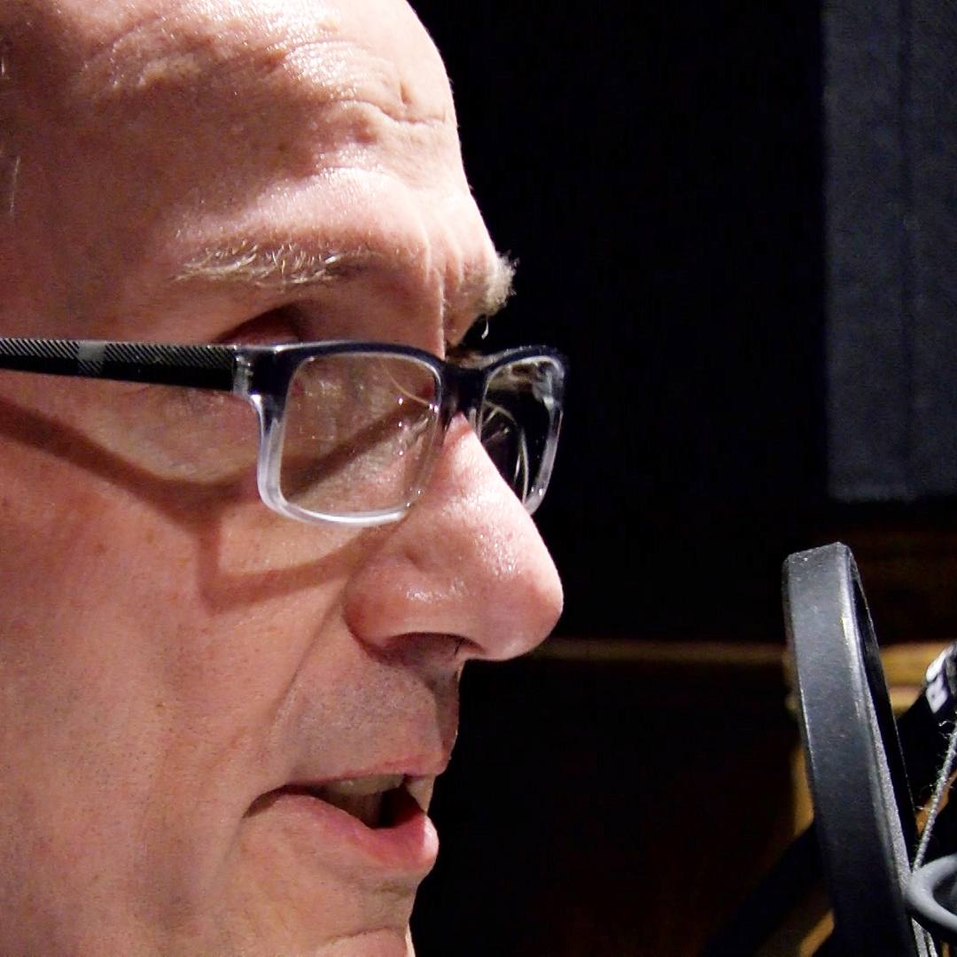 Cancer patient Jay Masters speaks into a microphone in a recording booth.