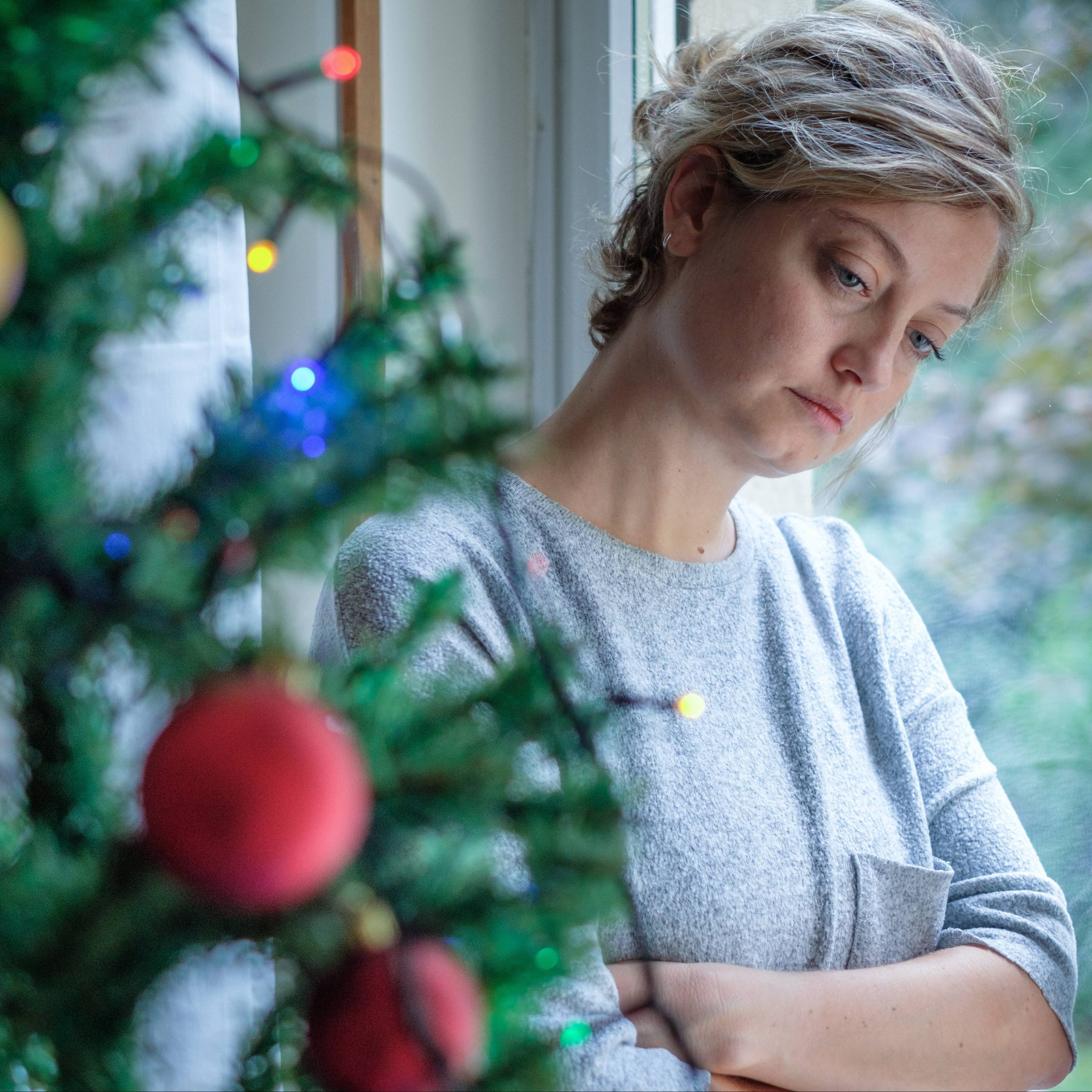 a young Caucasian woman looking sad and depressed, leaning against a glass door, with a decorated Christmas tree in the foreground